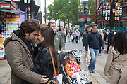 Couple embrace, looking into each other's eyes in Leicester Square, London, UK.