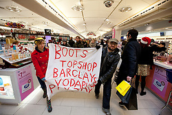 """© under license to London News Pictures. 18/12/2010: Approximately 25 protesters picketed Top Shop and other shops associated with Philip Green, Vodafone and Boots to highlight corporate tax-avoidance. Protesters walked through Boots, passed Christmas shoppers, with banners declaring it was """"Pay day"""""""