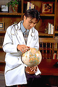 Korean medical physician intern doctor age 24 studying globe in office.  St Paul Minnesota USA