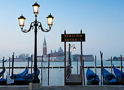 View of moored gondolas and street lamps beside Grand Canal at San Marco in Venice Italy