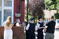 © Licensed to London News Pictures.<br /> 30/07/2020.  London, UK. Police talk to the members of public after a young man in aged in his mid-20 has been shot dead on a street in Edmonton, north London. Met Police say at 9:00pm yesterday, they were called to Beaconsfield Road. The victim was pronounced dead at the scene shortly after 10pm. The gunman remains at large - so far no arrests have been made.Photo credit: Marcin Nowak/LNP