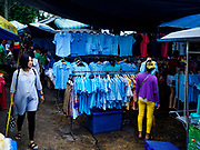 08 AUGUST 2018 - BANGKOK, THAILAND: People look at blue shirts at Khlong Toei Market in Bangkok. Blue is the official color of Queen Mother Sirikit, whose birthday is 12 August. Khlong Toei is the largest market in Thailand.     PHOTO BY JACK KURTZ