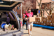 "27 FEBRUARY 2021 - DES MOINES, IOWA: Members of the Grand View University football team load emergency food boxes into a car during a touchless emergency food distribution at the John R. Grubb Community YMCA in Des Moines. The food distribution was organized by Farmers to Families and the YMCA. They had 1,000 boxes of emergency rations which included fresh fruit and vegetables, yogurt, chicken and hot dogs. They also had 1,000 gallons of milk. The neighborhood around the YMCA is a ""food desert,"" with no nearby grocery stores that sell healthy food. Food bank use in Iowa is up more than 60% since the start of the Coronavirus pandemic. Food bank officials estimate that 4 in 10 users are new users of emergency food pantries.        PHOTO BY JACK KURTZ"