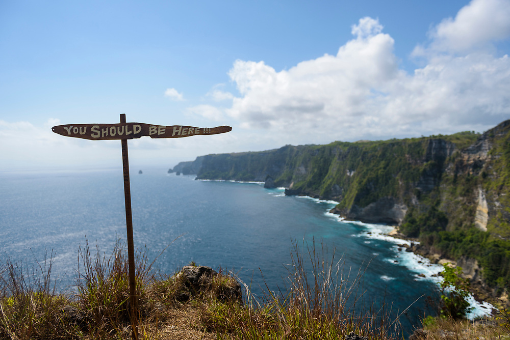 """Nusa Penida, Indonesia - September 30, 2017: A sign reads """"YOU SHOULD BE HERE"""" on a cliff above the sea at Manta Point on the scenic island of Nusa Penida in Indonesia"""