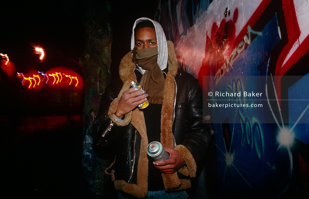 A masked youth is seen after spraying graffiti art on to a wall in the Notting Hill area of West London, England. We see his partially-obscured face while holding a spray can in one hand. It is a chilly night and the boy's breath is seen against the frosty night air. His graffiti art has taken him some hours to spray on this white wall and shows a glossy finish. The picture is anonymous because of the young man's face is unseen and generic, because we don't see where the wall might be located.