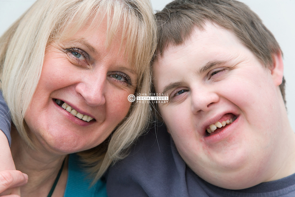 Mother and teenage with Downs Syndrome son having a cuddle,