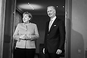Brussels Belgium  January 12 2017 King Filip of Belgium receives chancellor of Belgium Angela Merkel, after she received an honourable mention from two Belgian universities for her European politics and tolerance to refugees. shaking hands. A light in the backroom shines as an aureool, declaring Merkel holy