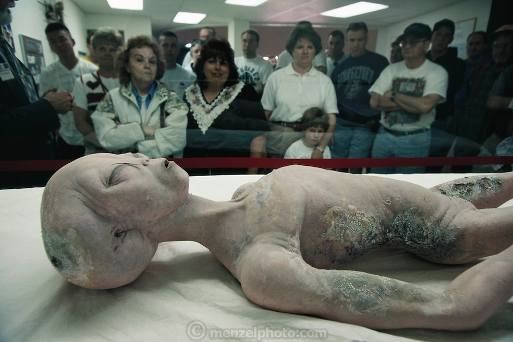 """Replica of an alien body (a movie prop donated to the museum) in the International UFO Museum and Research Center, 114 N. Main St., in downtown Roswell, New Mexico. Museum visitors begin their tour with a short talk by Dennis Balthaser, a """"certified MUFON UFO-ologist"""" (Mutual UFO Network). The Roswell incident started on 2 July 1947 when UFO sightings were reported during a thunderstorm. Next morning a rancher, Mac Brazel, discovered strange wreckage in a field. When the impact site was located, a UFO craft and alien bodies were allegedly found. On 8 July 1947, the Roswell Daily Record announced the capture of a flying saucer. (1997)."""