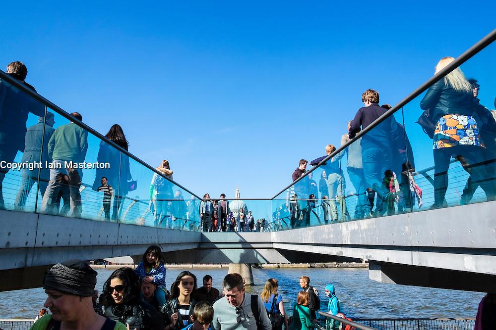 People crossing Millenium Bridge across River Thames in London United Kingdom