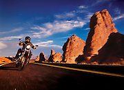A man on a motorcyle is goes for a ride on a windy road in the desert of Arizona
