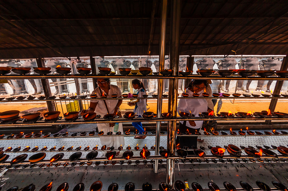 Burning oil lamps, Ruwanwelisaya Dagoba (Stupa) in the ancient city of Anuradhapura, Sri Lanka. Also known as the Ruwanweli Maha Seya, or Great Stupa is a sacred place of pilgrimage and worship in the ancient city of Anuradhapura.