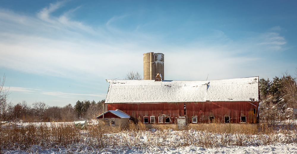 Snow covered old red barn on a sunny December day following first snow in Dane County, Wisconsin.