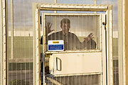 A prisoner waits outside his wing secured door to return to his cell. HMP/YOI Portland, Dorset. A resettlement prison with a capacity for 530 prisoners. Dorset, United Kingdom.