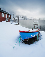 Small row boat surrounded by snow outside traditional Rorbu cabin, Toppøya, Moskenesøy, Lofoten Islands, Norway