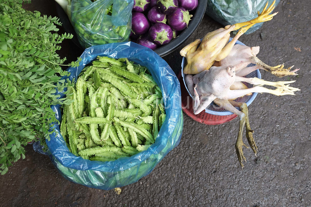 Fresh chickens and vegetables for sale at Phsar Kandal morning market in Phnom Penh, the capital city of Cambodia. A large variety of local products are available for sale in fresh markets all over Cambodia, all being sold on small individual stalls.