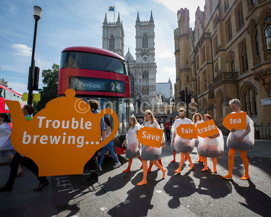 Human tea bags protest outside Sainsbury's AGM to highlight concern over supermarket's decision to replace Fairtrade tea on July 5th 2017 in London, United Kingdom.Campaigners dressed up as tea bags protest in front of a giant teapot as shareholders arrive for Sainsbury's annual general meeting. The human tea bags' message says 'Save Fairtrade Tea'. The stunt by Oxfam and CAFOD is part of a campaign launched by a coalition of charities. One of the main concerns is that farmers and workers who produce 'Fairly Traded' tea for Sainsbury's will no longer have direct control over how they spend the premium – an additional payment on the basic price intended to benefit them. Instead, they will have to apply to a board set up by Sainsbury's in London. London. United Kingdom.