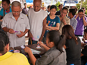 03 JULY 2011 - SAMUT PRAKAN, THAILAND:    Voters wait to pick up their ballots in Samut Prakan, Thailand, Sunday, July 3. More than 47,000,000 Thais were registered to vote in Sunday's election, which had turned into a referendum on the current government, led, by the Thai Democrats and the oppositionPheu Thai party. Pheu Thai is the latest political incarnation of ousted Thai Prime Minister Thaksin Shinawatra. PT is led by his youngest sister, Yingluck Shinawatra, who is the party's candidate for Prime Minister. Exit polling by three Thai polling firms showed Pheu Thai winning a landslide election.     PHOTO BY JACK KURTZ