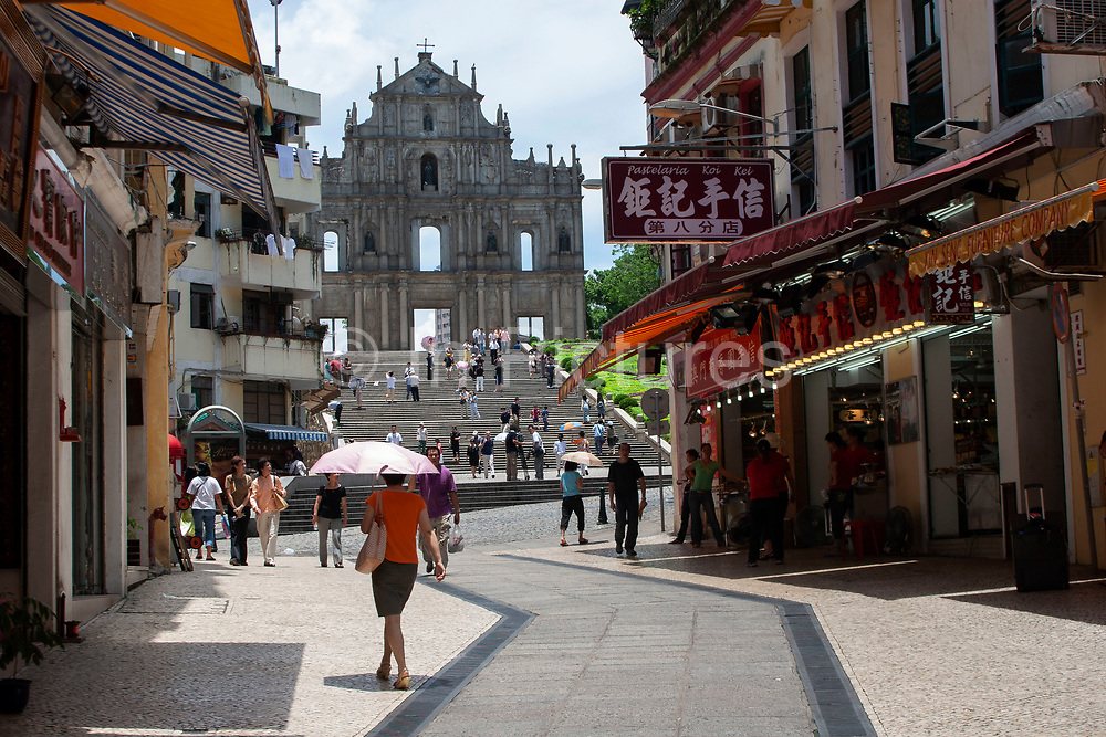 Macaos famous Facade in Macau, China. The Cathedral of Sain Paul, also known as Saint Pauls Cathedral. This ruin remains Macaos most famous tourist site. Tourists gather on the steps leading up to take pictures of this stone facade, intricately carved by Japanese monks. Built between 1582 and 1602, the facade was excaated and protected in the 1990s, while the crypt was also revealed. Macau is an autonomous region on the south coast of China, across from Hong Kong. A Portuguese territory until 1999, it reflects a mix of cultural influences.