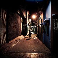 Young girl walks barefoot down alleyway late at night, Saigon, Vietnam