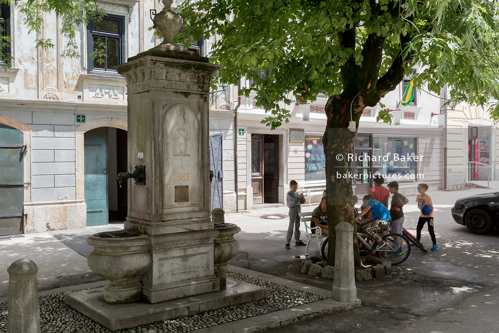 A town fountain and local children in a rural central Slovenian town, on 25th June 2018, in Skofja Loka, Slovenia.