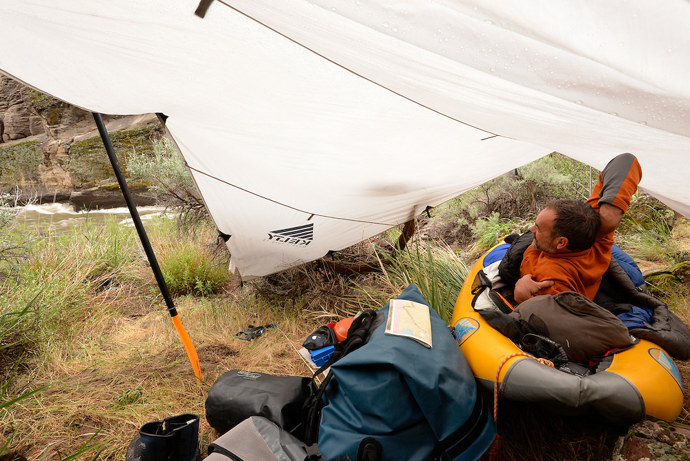 Kayaker waking from a night sleeping in inflatable kayak under a tarp on a trip down Idaho's Bruneau River.