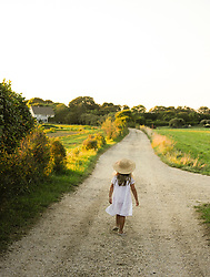 little girl dressed in beautiful clothes walking down a dirt road in The Hamptons