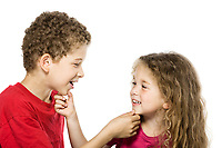 caucasian little boy and girl portrait playing isolated studio on white background