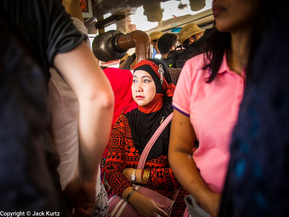 18 AUGUST 2013 - BANGKOK, THAILAND:      A Muslim woman rides the Chao Phraya Express Boat in Bangkok, Thailand. Thailand has emerged as a popular vacation destination for people from around the world. Thais are traditionally tolerant of other religions and lifestyles and that tolerance has propelled Thailand into the first rank of tourist destinations for gays and straights from the US and Europe and Muslims and Jews from the Middle East.    PHOTO BY JACK KURTZ
