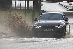 © Licensed to London News Pictures. 03/02/2021. London, UK. A car drives through a large puddle in Greenwich, South East London . Yellow weather warnings for rain and snow are in place in parts of the UK. Photo credit: George Cracknell Wright/LNP
