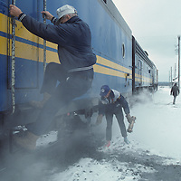 Canada, Ontario, Engineers climbs into locomotive in cloud of steam on VIA Rail passenger train at train station in Ignace