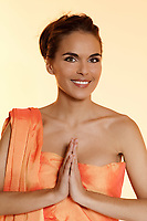 studio shot portrait of a beautiful brunette green eyes young woman wearing orange sari