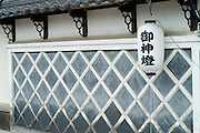 """An outer wall of a Japanese house done in the style of a castle. The lantern reads """"Goshinto"""", meaning that this is a """"lantern for god"""". Artists also have these for good luck."""