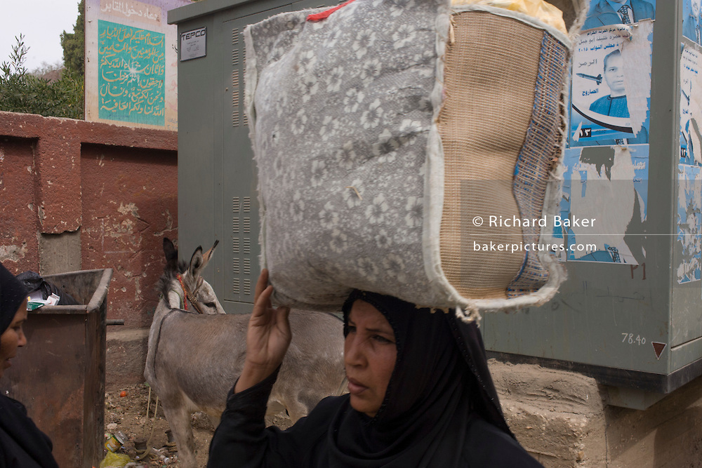 A local woman carries her purchases at the weekly market at Qurna, a village on the West Bank of Luxor, Nile Valley, Egypt.
