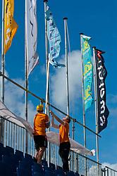 25-08-2010 VOLLEYBAL: SWATCH FIVB WORLD TOUR: SCHEVENINGEN<br /> Vlaggen worden opgehangen bij de tribnunes op het Center Court<br /> ©2010-WWW.FOTOHOOGENDOORN.NL / Peter Schalk