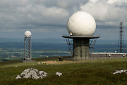 Radar station on top of Titterstone Clee Hill on 10th May 2021 in Cleedownton, United Kingdom. Titterstone Clee Hill, sometimes referred to as Titterstone Clee or, incorrectly, Clee Hill, is a prominent hill in the rural English county of Shropshire, rising at the summit to 533 metres above sea level. It is one of the Clee Hills, in the Shropshire Hills Area of Outstanding Natural Beauty. Most of the summit of the hill is affected by man-made activity, the result of hill fort construction during the Bronze and Iron Ages and, more recently, by years of mining for coal and quarrying for dolerite, known locally as dhustone, for use in road-building. Many derelict quarry buildings scattered over the hill are of industrial archaeological interest as very early examples of the use of reinforced concrete. Several radar domes and towers operate on the summit of the hill. The largest of the radar arrays is part of the National Air Traffic Services NATS radar network, and covers one of 30 overlapping regions of UK airspace. The one on Titterstone Clee monitors all aircraft within a 100-mile radius.