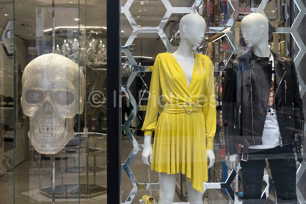 Large diamond skull window display in the shop window of one of the exclusive fashion shops on Bond Street on 1st July 2020 in London, United Kingdom.  It is one of the principal streets in the West End shopping district and is more upmarket. It has been a fashionable shopping street since the 18th century. Technically Bond Street does not exist: The southern section is known as Old Bond Street, and the northern section, which is rather more than half the total length, is known as New Bond Street. The rich and wealthy shop here mostly for high end fashion.