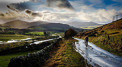 A lone cyclist on a road above the flooded Tweed valley after heavy rain near Broughton in the Scottish Borders.<br /> <br /> (c) ANDREW WILSON | www.EdinburghElitemedia.co.uk
