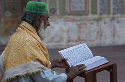 June 1, 2017 - Lahore, Punjab, Pakistan - An old man reading holy Quran during the holy month of Ramzan-ul-mubarak at the historical Wazir Khan Mosque. Muslims around the world celebrate the holy month of Ramzan by praying during the night time and abstaining from eating, drinking, and sexual acts daily between sunrise and sunset. Ramzan is the ninth month in the Islamic calendar and it is believed that the Koran's first verse was revealed during its last 10 nights. (Credit Image: © Rana Sajid Hussain/Pacific Press via ZUMA Wire)