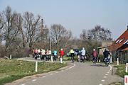 Nederland,Ooijpolder, 20-2-2019 Een groep oudere fietsers . Mensen, ouderen, maken een fietstochtje over de dijk langs de Waal, Rijn . Soms is het erg druk op de dijk met verschillende vormen van verkeer waardoor het fietsen en wandelen gevaarlijk kan zijn .Het is een mooie dag met zon en een blauwe onbewolkte lucht. FOTO: FLIP FRANSSEN