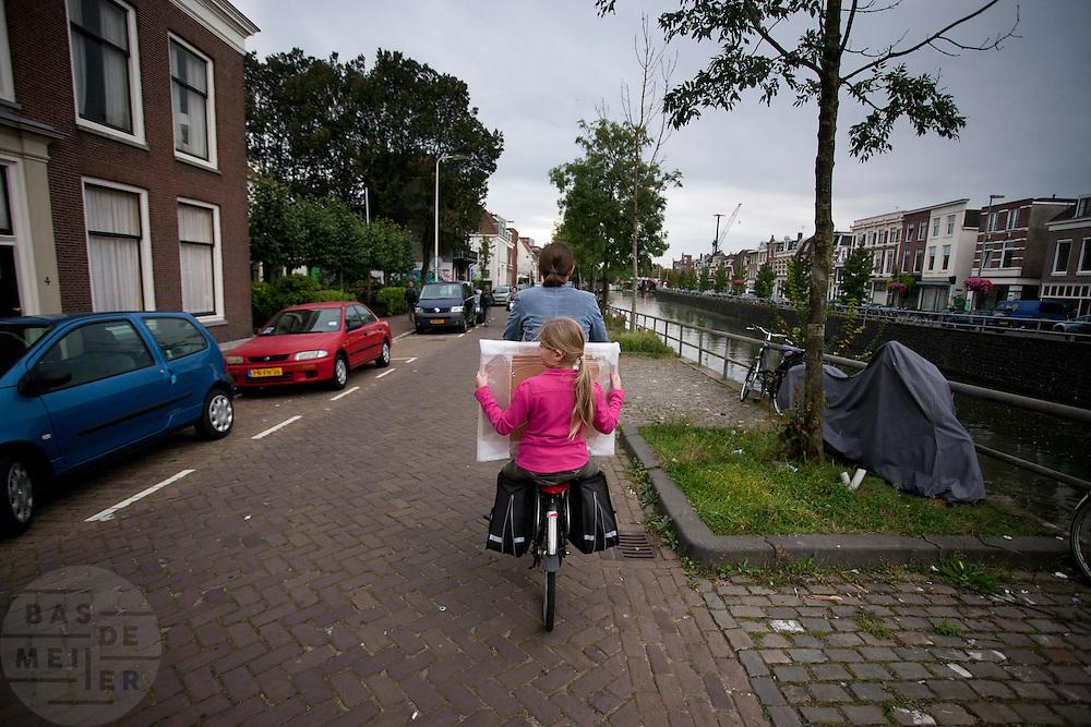 Een meisje houdt achterop de fiets bij haar moeder een schilderij vast.<br /> <br /> A girl is sitting with a painting on the back of a bike in Utrecht.