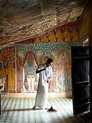 Groundsman sweeping the floor of a Buddhist temple in the Mulkirigala Monastery, Sri Lanka
