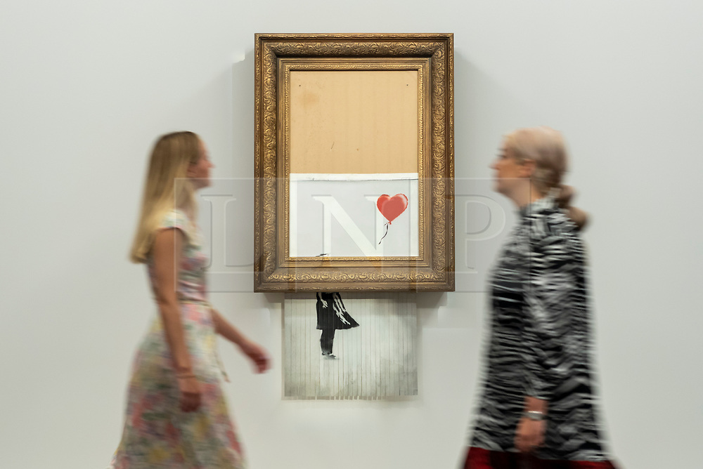 """© Licensed to London News Pictures. 03/09/2021. LONDON, UK.  **UNDER EMBARGO UNTIL FRIDAY 3 SEPTEMBER 2021, 12PM BST** Staff pass """"Love Is in the Bin"""" by Banksy at a preview at Sotheby's.  The painting, originally known as """"Girl with Balloon"""", was famously shredded by the artist in Sotheby's London auction room in 2018 after being sold for £1,042,000.  The resulting artwork was later renamed """"Love Is in the Bin"""" and will be offered for sale in Sotheby's contemporary art evening auction on October 14 with an estimate of £4-6 million.  Photo credit: Stephen Chung/LNP"""