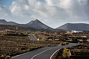 A road runs through Los Volcanes Natural Park on 27th November 2020 in Lanzarote, Spain. The island was transformed by huge volcanic eruptions from 1731-36, which created the area now known as Timanfaya Natural Park, on the right, and created the islands dramatic landscape. .