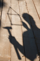 Shadow of person on wood  holding hammer and folding ruler