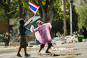 02 DECEMBER 2013 - BANGKOK, THAILAND:   Anti-government protestors throw rocks at police positions in Bangkok. Anti-government protestors and Thai police continued to face off Monday for a second day. Police used tear gas, water cannons and rubber bullets against protestors who charged their positions near the barriers on Chamai Maruchet bridge on Phitsanulok Road, which leads to the Government House.   PHOTO BY JACK KURTZ