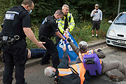 Police officers drag Insulate Britain climate activists out of a slip road from the M25 which they had blocked, causing a long tailback on the motorway, as part of a new campaign intended to push the UK government to make significant legislative change to start lowering emissions on 13th September 2021 in Godstone, United Kingdom. The activists, who wrote to Prime Minister Boris Johnson on 13th August, are demanding that the government immediately promises both to fully fund and ensure the insulation of all social housing in Britain by 2025 and to produce within four months a legally binding national plan to fully fund and ensure the full low-energy and low-carbon whole-house retrofit, with no externalised costs, of all homes in Britain by 2030 as part of a just transition to full decarbonisation of all parts of society and the economy.