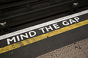 Mind the gap tube platform warning sign on a London Underground station platform in London, United Kingdom. Mind the gap is an audible or visual warning phrase issued to rail passengers to take caution while crossing the horizontal, and in some cases vertical, gap between the train door and the station platform.