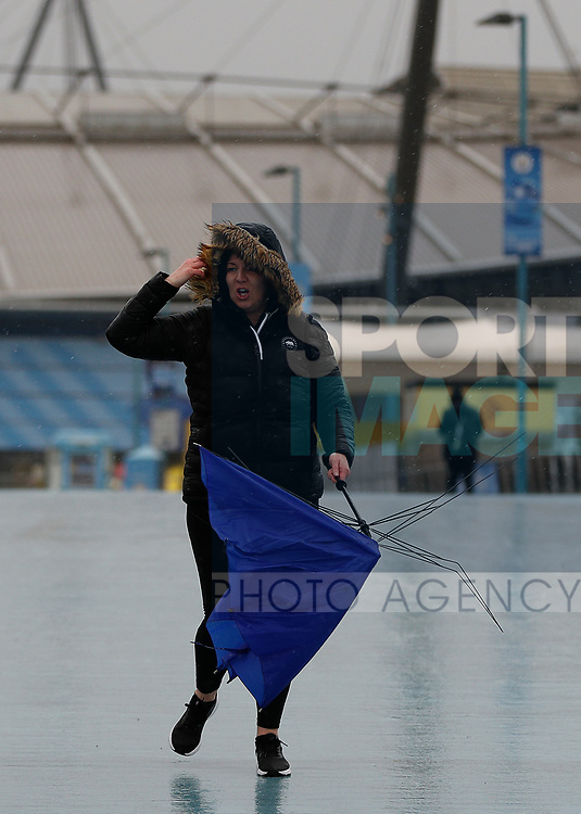 A fans with a broken umbrella leaves after the Premier League match between Manchester City and West Ham United was postponed because of weather conditions at the Etihad Stadium, Manchester. Picture date: 9th February 2020. Picture credit should read: Darren Staples/Sportimage