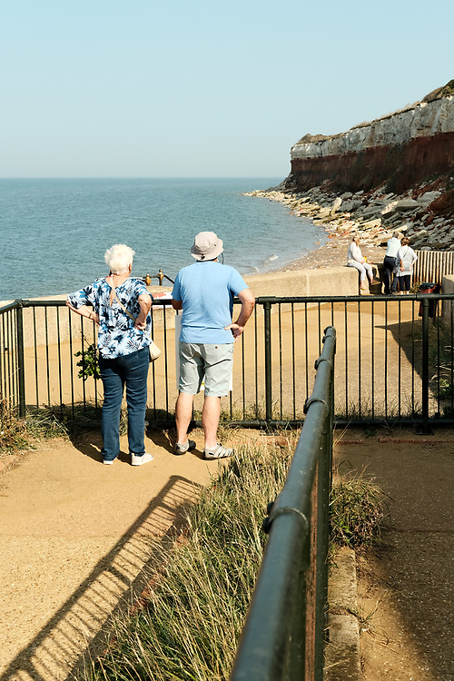 Lady & Gentleman stand on a footpath admiring the red and white striped cliffs at Hunstanton. Taken on the last hot day of the Summer in Hunstanton Norfolk, the first summer in the UK during the COVID-19 pandemic.<br />  <br /> Photo by Jonathan J Fussell, COPYRIGHT 2020