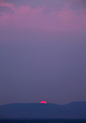 Red sun setting over mountain.